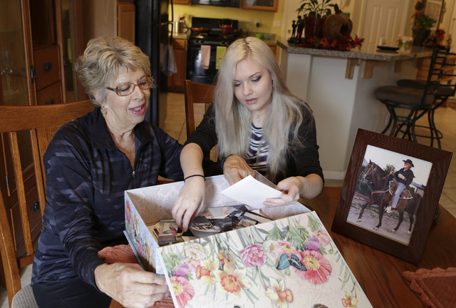 Cancer advocate Sherry Jasperson, left, watches photos of her husband John with her granddaughter Kate Rasmussen, 18, at their home Friday, Oct. 28, 2016, in Las Vegas. Sherry is the state lead fo ...