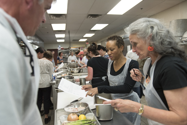 Participants Marleece Barber, center, Mary Dickson, right, and Mike Deneff prepare a meal based on patient casework during a cooking class for the Primary Care Cardiometabolic Risk Summit at the C ...