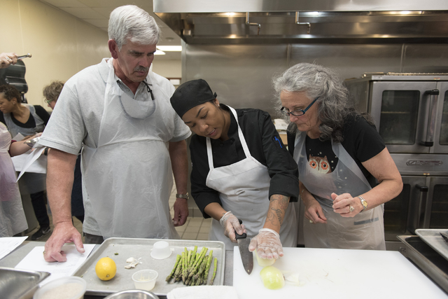 Chef Marisa Rodriguez with the Culinary Academy of Las Vegas, center, assists participants Mary Dickson, right, and Mike Deneff during a cooking class for the Primary Care Cardiometabolic Risk Sum ...