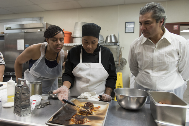 Chef Marisa Rodriguez with the Culinary Academy of Las Vegas, center, assists participants during a cooking class for the Primary Care Cardiometabolic Risk Summit at the academy, Sunday, Oct. 16,  ...