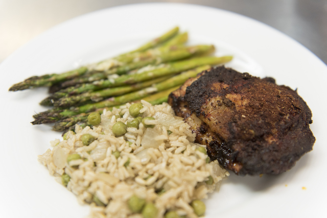 A plate of Moroccan spiced broiled chicken, roasted asparagus and brown basmati rice and peas is seen during a cooking class for the Primary Care Cardiometabolic Risk Summit at the Culinary Academ ...