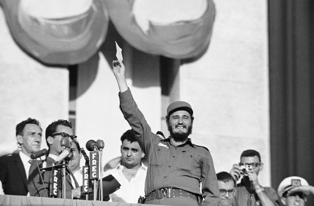 Happy Fidel Castro waves twenty million-dollar check representing funds seized from Batista and his supporters, which Cuban government turned over to him for agrarian reform program, July 26, 1959 ...