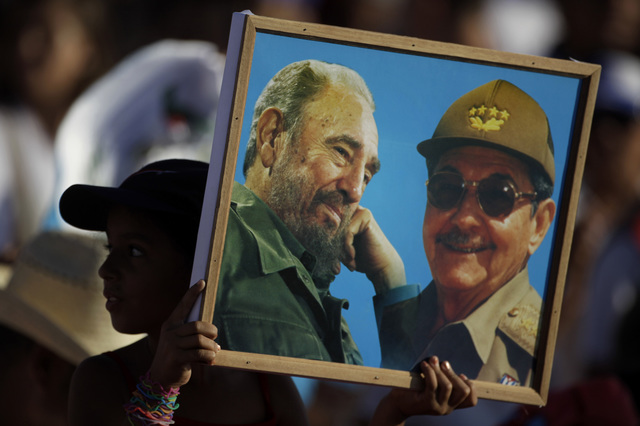 A girl holds up a photo of Cuba's revolutionary leader Fidel Castro and his brother, President Raul Castro, at the May Day celebration in Revolution Square in Havana, Cuba, Sunday May 1, 2011. (AP ...