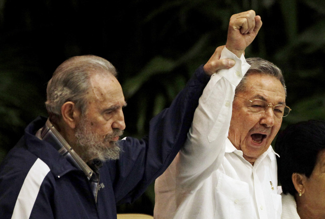 In this April 19, 2011 file photo, Fidel Castro, left, raises his brother's hand, Cuba's President Raul Castro, center, as they sing the anthem of international socialism during the 6th Communist  ...