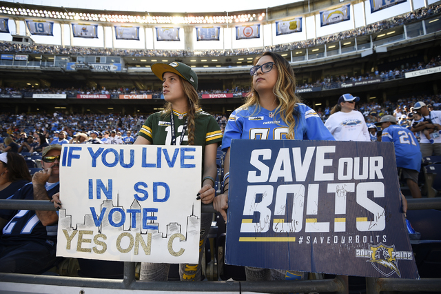 Fans hold signs in support of a local ballot measure to help fund a new stadium for the San Diego Chargers before an NFL football game between the Chargers and the Tennessee Titans Sunday, Nov. 6, ...