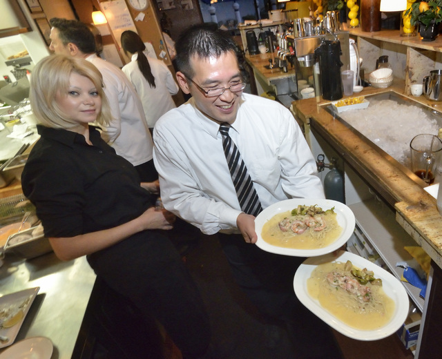 Server Tracy Terai, right, takes food to customers at Chef Marc's Trattoria at 8615 W. Sahara Ave. in Las Vegas on Saturday, Oct. 29, 2016. Bill Hughes/Las Vegas Review-Journal