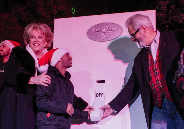 Las Vegas Mayor Carolyn Goodman, left, OVIP Reggie, center, and President and CEO of Opportunity Village, Bob Brown, flip the switch to light the tree during the 25th tree lighting ceremony at Opp ...