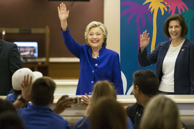 Democratic presidential nominee Hillary Clinton, left, with U.S. Senate candidate Catherine Cortez Masto wave as they enter the room to meet with employees at The Mirage hotel-casino during a surp ...