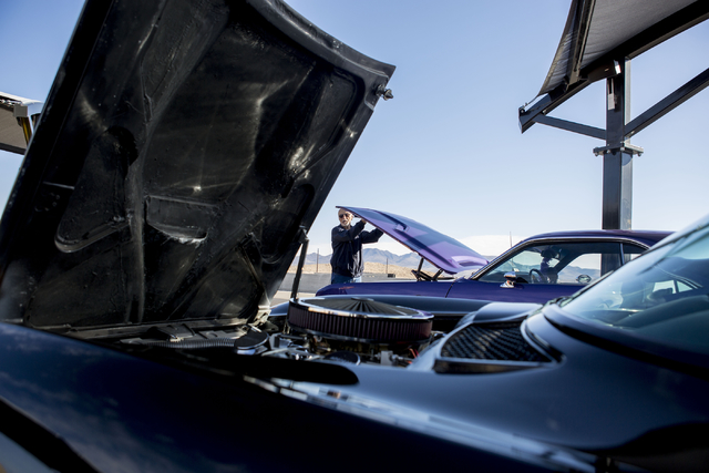 Steve Passos, car enthusiast, closes the hood of his 1970 Dodge Challenger,  Saturday, Nov. 26, 2016, during Cars and Coffee, which meets every Saturday morning at SPEEDVEGAS in Las Vegas. Elizabe ...