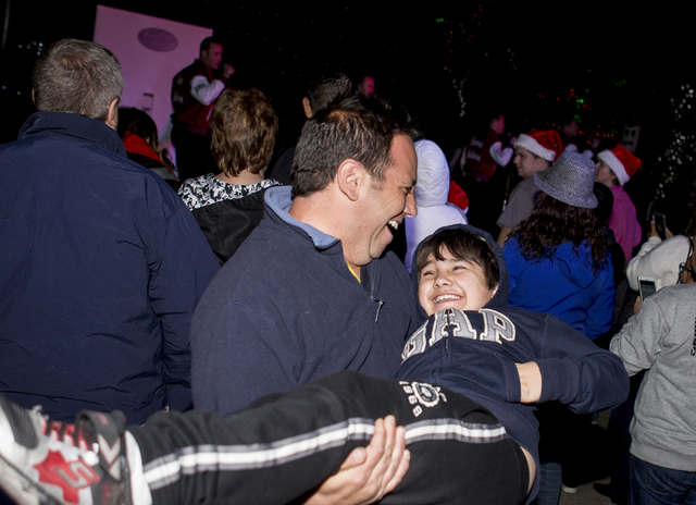 Matthew Kluger dances with his son Henry, 8, while the singing group Human Nature preforms during the 25th annual tree lighting ceremony at Opportunity Village in a helicopter, Friday, Nov. 25, 20 ...