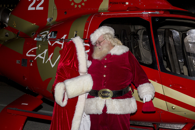Santa Clause is greeted by Mrs. Clause after arriving for the 25th annual tree lighting ceremony at Opportunity Village in a helicopter, Friday, Nov. 25, 2016, Las Vegas. (Elizabeth Page Brumley/L ...
