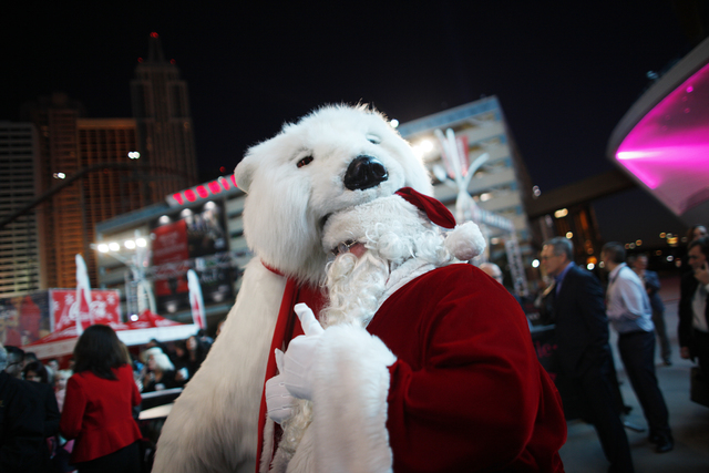 The Coca-Cola Bear pretends to eat Santa Claus' head on Monday, Nov. 21, 2016, at the tree lighting ceremony at The Park in Las Vegas. Rachel Aston/Las Vegas Review-Journal Follow @rookie__rae