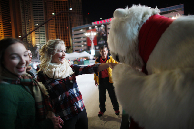 Michelle Rudzki has her hand kissed by the Coca-Cola bear on Monday, Nov. 21, 2016, at the tree lighting ceremony at The Park in Las Vegas. Rachel Aston/Las Vegas Review-Journal Follow @rookie__rae