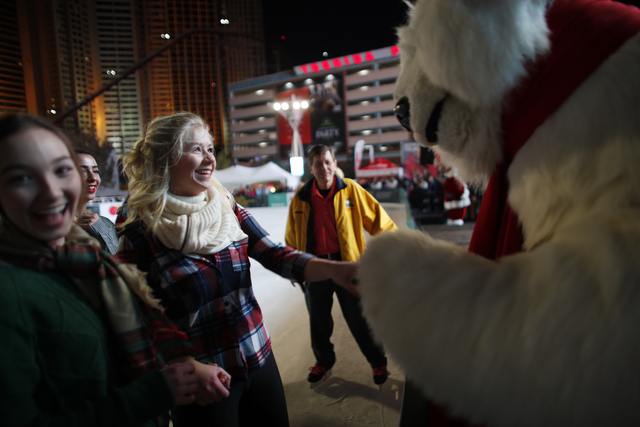 Michelle Rudzki holds hands with the Coca-Cola bear on Monday, Nov. 21, 2016, at the tree lighting ceremony at The Park in Las Vegas. Rachel Aston/Las Vegas Review-Journal Follow @rookie__rae