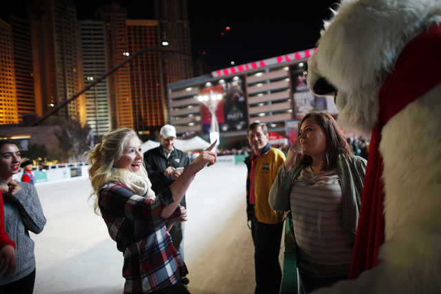 Michelle Rudzki points at the Coca-Cola bear on Monday, Nov. 21, 2016, at the tree lighting ceremony at The Park in Las Vegas. Rachel Aston/Las Vegas Review-Journal Follow @rookie__rae