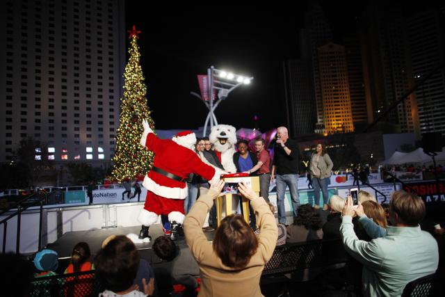 Santa Claus, the Coca-Cola Bear, Chet Buchanan, and a group of military veterans press the button to light the tree on Monday, Nov. 21, 2016, at The Park in Las Vegas. Rachel Aston/Las Vegas Revie ...