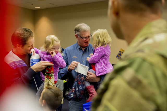 Henderson Mayor Andy Hafen, right, holds his granddaughter Aly Hafen, with his son A.K. Hafen, holding his daughter Ava, while they fill stockings for troops serving overseas during the 8th annual ...