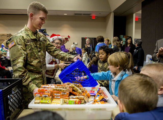 "Cody Reeves, of the U.S. Army, volunteers at the food station while students from Gordon McCaw Elementary School fill stockings for active troops overseas during the 8th annual ""Stockings ..."