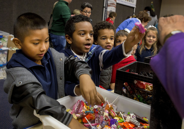 "Elmer Gomez, 6, Yona Dhandawit, 6,Emmanuel Ayim, 6, students from Gordon McCaw Elementary School, fill stockings for active troops overseas during the 8th annual ""Stockings for our Troops ..."