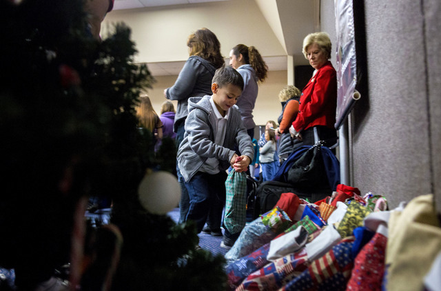 "Frederick J. Enrequez Jr., 6, a student from Gordon McCaw Elementary School, places his filled stocking for active troops overseas under the Christmas tree during the 8th annual ""Stocking ..."