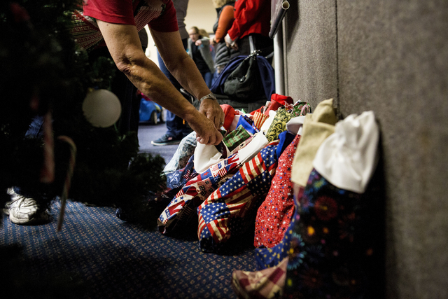"A volunteer during the 8th annual ""Stockings for our Troops,"" straightens the filled stockings for active troops overseas, Henderson City Hall, Tuesday, Nov. 29, 2016, in Henders ..."