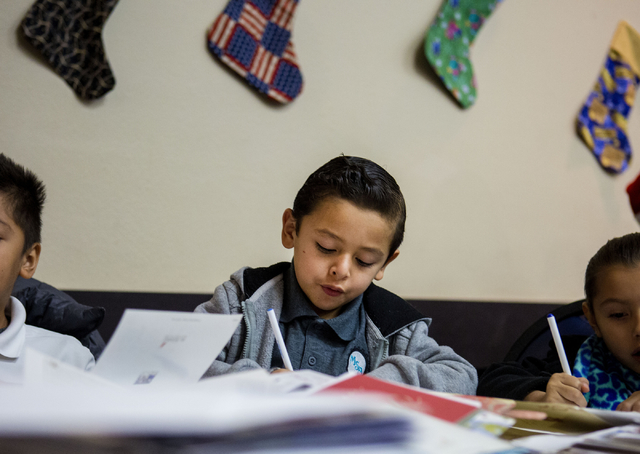 "David Espino, 6, a student from Gordon McCaw Elementary School, writes a letter for an active troop overseas during the 8th annual ""Stockings for our Troops,"" at Henderson City H ..."
