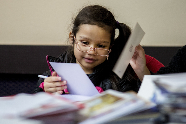 "Aurora Guerir-Bolt, 6, a student from Gordon McCaw Elementary School, writes a letter for an active troop overseas during the 8th annual ""Stockings for our Troops,"" at Henderson  ..."