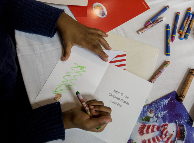 "A student from Gordon McCaw Elementary School, writes a letter for an active troop overseas during the 8th annual ""Stockings for our Troops,"" at Henderson City Hall, Tuesday, Nov ..."