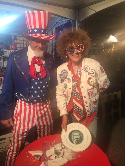 """Joined by Uncle Sam (alias artist Stewart Freshwater), artist Diane Bush invites October First Friday visitors to """"Let America Break Again"""" by smashing plates. (Corey Fagan/First Friday Foundation)"""