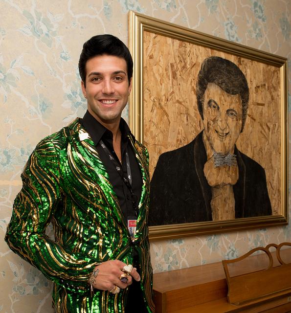 Michael Orsini poses next to a painting of Liberace. (Tonya Harvey/Real Estate Millions)
