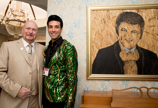 Liberace owner Martyn Ravenhill and Michael Orsini stand next to a painting of Liberace. (Tonya Harvey/Real Estate Millions)