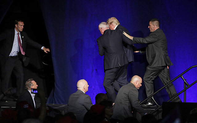 Members of the Secret Service rush Republican presidential candidate Donald Trump off the stage at a campaign rally in Reno, Nev., on Saturday, Nov. 5, 2016. (John Locher/The Associated Press)