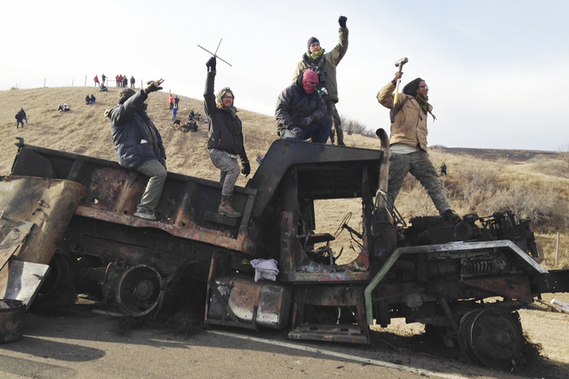 FILE - In this Monday, Nov. 21, 2016, file photo, protesters against the Dakota Access oil pipeline stand on a burned-out truck near Cannon Ball, N.D., that they removed from a long-closed bridge  ...