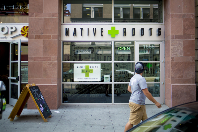 A pedestrian walks passed Native Roots Dispensary where different forms of recreational marijuana can be purchased in Denver, Wednesday, Aug. 31, 2016. (Elizabeth Page Brumley/Las Vegas Review-Jou ...