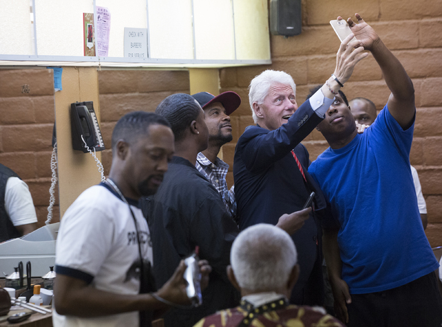 Former President Bill Clinton takes a selfie with D'Mario Osley, right, at Hair Unlimited on Thursday, Nov. 3, 2016, in Las Vegas. President Clinton was in Las Vegas for a rally at Cox Pavilion fo ...