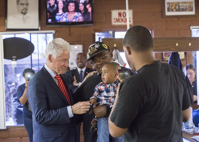 Former President Bill Clinton shakes hands with Christian Smith, 2, at Hair Unlimited on Thursday, Nov. 3, 2016, in Las Vegas. President Clinton was in Las Vegas for a rally at Cox Pavilion for hi ...