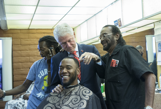 Former President Bill Clinton helps Mac Smith, Jr., right, owner of Hair Unlimited, cut D.J. Anderson's hair on Thursday, Nov. 3, 2016, in Las Vegas. President Clinton was in Las Vegas for a rally ...