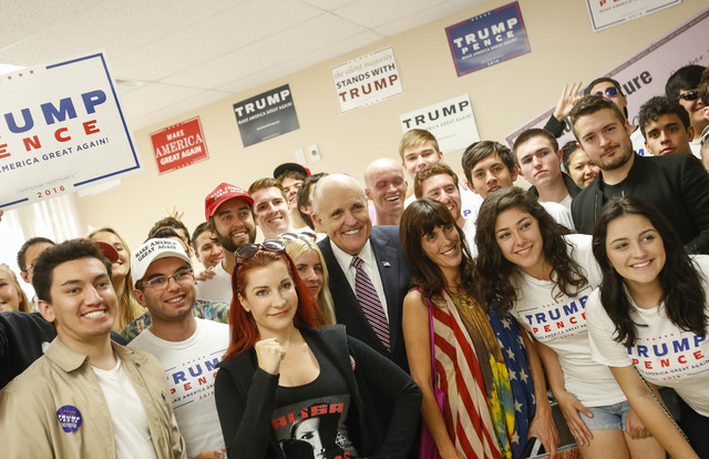 Lawyer and former New York City Mayor Rudy Giuliani, center, poses for a photo with a group of volunteers after speaking to supporters of Republican presidential candidate Donald Trump during a ca ...