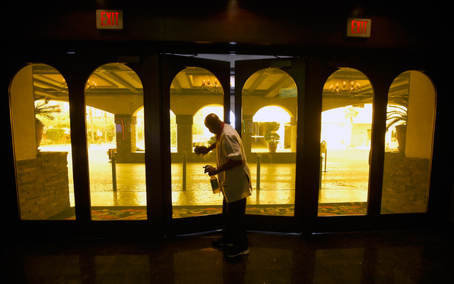 A hotel maintenance worker keeps the front doors at the El Cortez clean on Thursday, Oct. 27, 2016, in Las Vegas. The family-owned downtown institution is celebrating its 75th anniversary. It orig ...