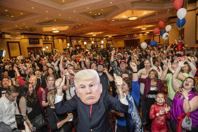 Ted Mueller, middle/mask, leads a room full Donald Trump supporters in a cheer after the Republican Presidential nominee was officially announced as the 45th President of the United States at an e ...