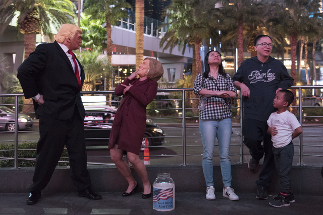 Donald Trump and Hillary Clinton impersonators Rafael and Corina Almodovar act around pedestrians watching CNN's live coverage of the presidential election on the screens outside of the Miracle Mi ...