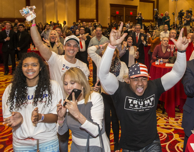 Trump supporter Michael Armstrong, right, cheers as initial  results are announced at an election night event hosted by the Nevada Republican Party at South Point hotel-casino on Tues, Nov. 8, 201 ...