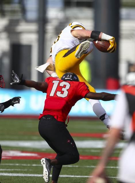 Wyoming tight end Jacob Hollister (88) jumps over UNLV defensive back Tim Hough (13) while running the ball during a football game at Sam Boyd Stadium in Las Vegas on Saturday, Nov. 12, 2016. (Cha ...
