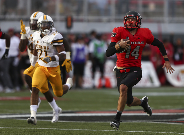 UNLV quarterback Kurt Palandech (14) runs the ball to score a touchdown during a football game against Wyoming at Sam Boyd Stadium in Las Vegas on Saturday, Nov. 12, 2016. UNLV defeated Wyoming 69 ...