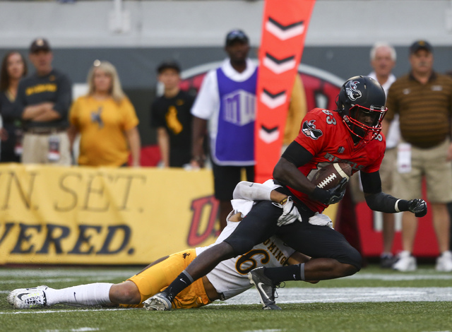 UNLV wide receiver Devonte Boyd (83) is tackled by Wyoming defensive back Marcus Epps (6) during a football game against Wyoming at Sam Boyd Stadium in Las Vegas on Saturday, Nov. 12, 2016. UNLV d ...