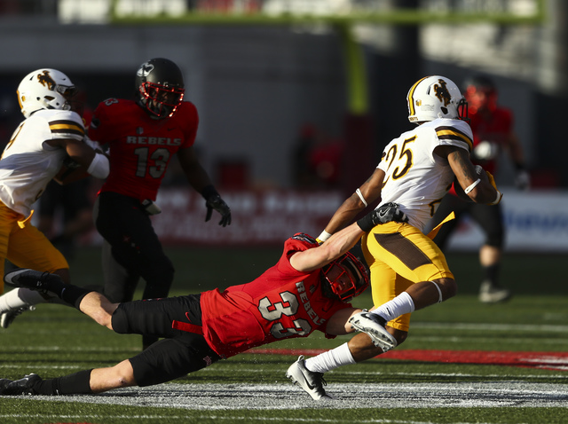 UNLV defensive back Dalton Baker (33) takes down Wyoming wide receiver Austin Conway (25) during a football game at Sam Boyd Stadium in Las Vegas on Saturday, Nov. 12, 2016. UNLV defeated Wyoming  ...