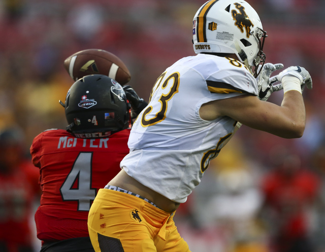 UNLV defensive back Torry McTyer (4) intercepts a pass intended for Wyoming wide receiver Jake Maulhardt (83) during a football game against Wyoming at Sam Boyd Stadium in Las Vegas on Saturday, N ...