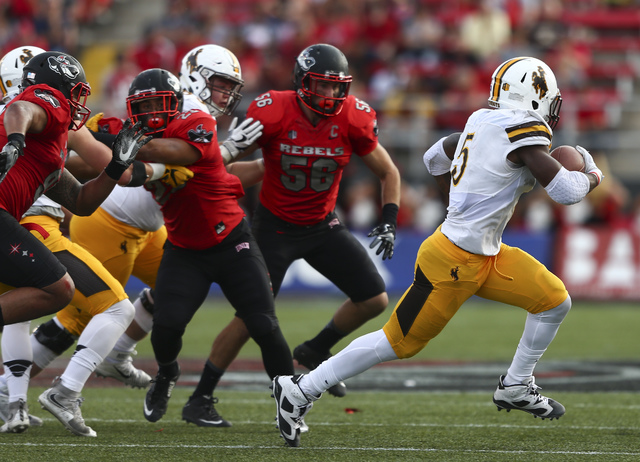 Wyoming running back Brian Hill (5) gets past UNLV defense during a football game at Sam Boyd Stadium in Las Vegas on Saturday, Nov. 12, 2016. UNLV defeated Wyoming 69-66 in triple overtime. Chase ...