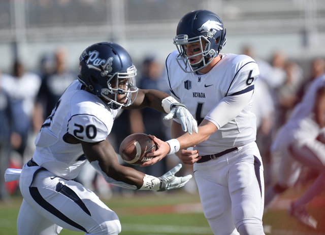 Nevada Wolf Pack quarterback Ty Gangi (6) hands the ball off to Nevada Wolf Pack running back James Butler (20) during the UNLV Nevada football game at Sam Boyd Stadium in Las Vegas on Saturday, N ...
