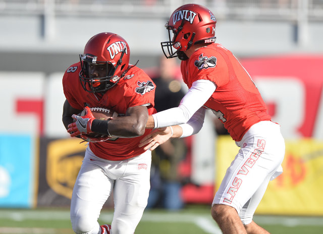 UNLV Rebels quarterback Kurt Palandech (14) hands the ball off to UNLV Rebels running back Charles Williams (8) during the UNLV Nevada football game at Sam Boyd Stadium in Las Vegas on Saturday, N ...